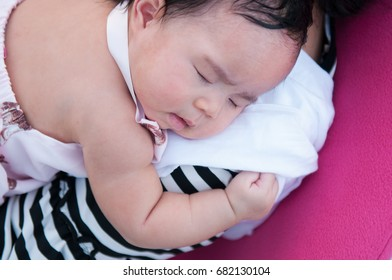 Mother holding her newborn baby in sexy dress while her was sleeping. Mother day bonding concept with newborn baby nursing.