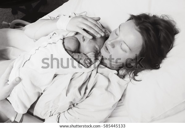 Mother holding her newborn baby child after labor in a hospital. Mother giving birth to a baby boy. Black and white photo.