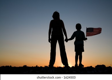Mother holding her son and son holding an American flag at sunset.