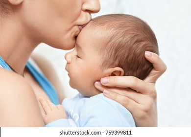 c93d8aedc3cb mother holding and kissing newborn baby. Maternal care & motherhood concept