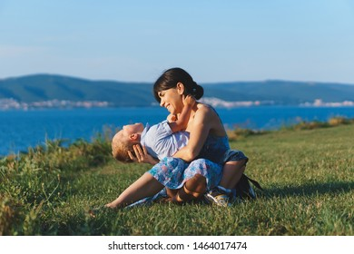 mother holding laughing son in hands on meadow