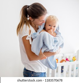 Mother holding little baby wrapped in towel after bath, hugging and kissing