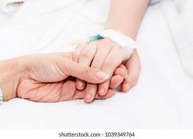 Mother holding little girl hand with IV saline intravenous in hospital
