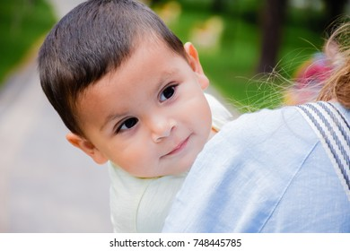 Mother holding little latin boy with content facial expression.