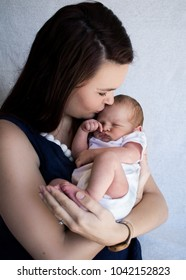 Mother holding newborn baby kissing on the forehead close up portrait.