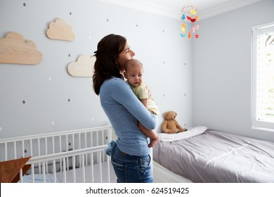 Mother Holding Newborn Baby Son In Nursery
