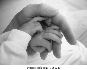 Mother holding newborn's hands