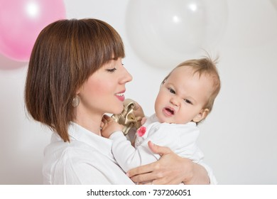 Mother holding an one year old baby daughter; baby girl trying to slip away from mother's embrace, feeling uncomfortable