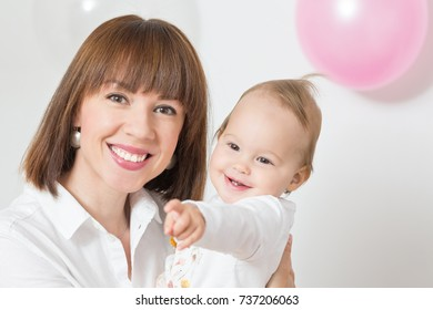 Mother holding an one year old baby daughter and smiling, baby girl pointing her finger