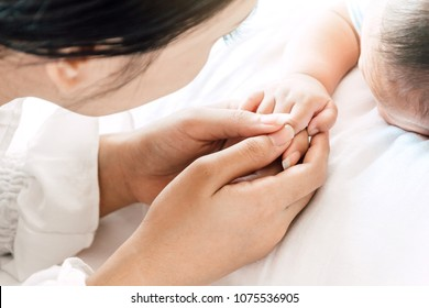 Mother holding sleeping baby hand on white bed.Love of family concept