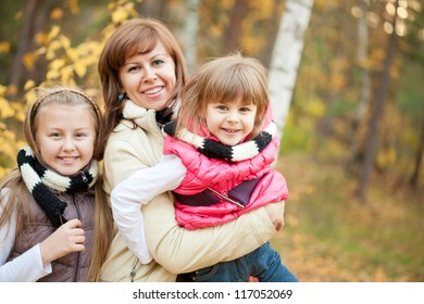 Mother holding small girl with daughter near by at autumn