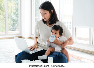 Mother holds the baby, drinks milk while working through the laptop at home.