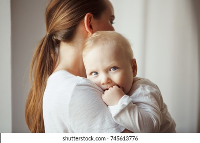 Mother holds baby with serous face in her arms