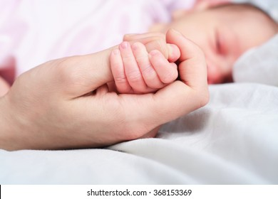 mother holds hand of her sleeping baby, closeup