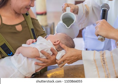 Mother holds new born baby boy as priest pours holy water over his head during baptism.