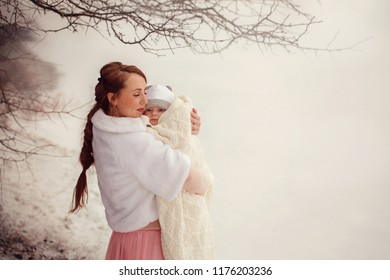 Mother holds on hands her little baby on winter walk outdoors