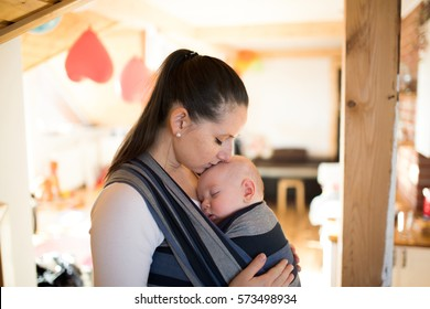 Mother at home with her son in sling, kissing him