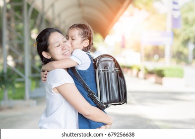 mother hug and kiss cute girl student before go to school, love and education concept