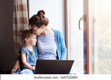 Mother hug and kiss daughter. Working mom works from home office. Woman and cute child sitting on window sill. Freelancer using laptop and the Internet. Female business, kindness, love. Copy space
