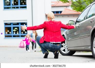 Mother hugging child after bringing her to school