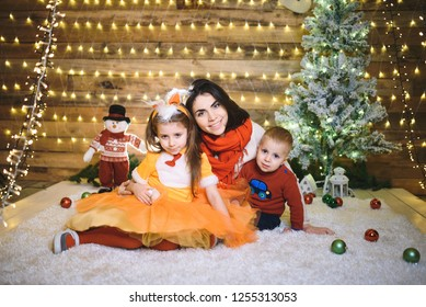 mother hugging children at christmas tree