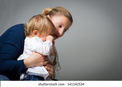 Mother hugging and comforting her little baby girl that is crying.