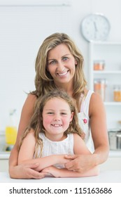 Mother hugging daughter in the kitchen while they look into the camera