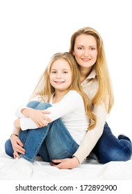 Mother hugging daughter sitting on the floor. Studio photo on white background.