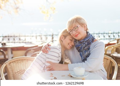 Mother is hugging her adult daughter. Beautiful women in cozy street cafe outdoor. Happy senior woman is smiling. Girl is enjoying kindness, warm hands, care, family love.