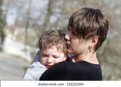 Mother hugging her crying son in the park