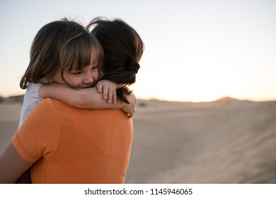 Mother hugging her little cute daughter on sand dune during sunset - detail