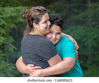 A mother is hugging her son
