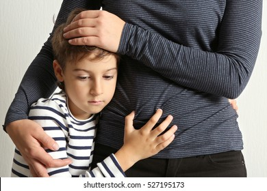 Mother hugging sad little boy, close up view