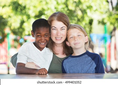 Mother hugging and sitting in between adopted child and son at table in park