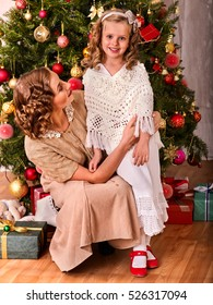 Mother hugs daughter on Christmas morning. Happy girl on the background of the Christmas tree. Happy family. Retro style.
