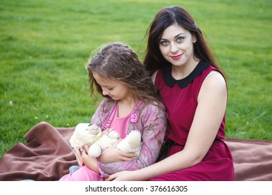 Mother hugs daughter in the park