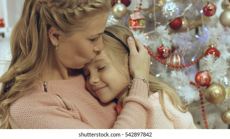 Mother hugs her little daughter in a Christmas atmosphere