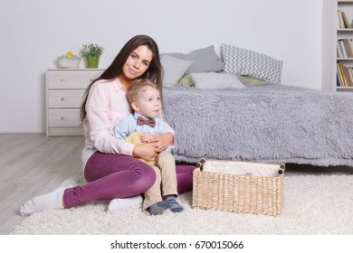 Mother hugs her little son in cozy bedroom with basket, toys at home