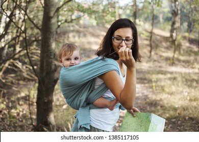 Mother with infant son in ergonomic sling, babywearing while hiking in the forest.