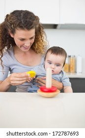 Mother with innocent baby boy looking at toys in kitchen