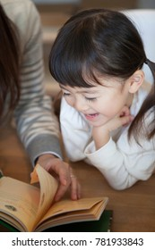Mother and a Japanese girl reading a book