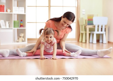 Mother and kid daughter doing fitness exercises on mat at home.