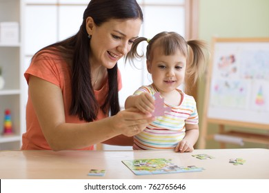 mother and kid daughter doing playing puzzle toy together on the table in children room