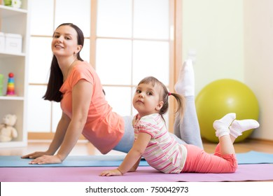 Mother and kid daughter doing yoga exercises on floor in the room at home. Family having fun indoors with fitness.