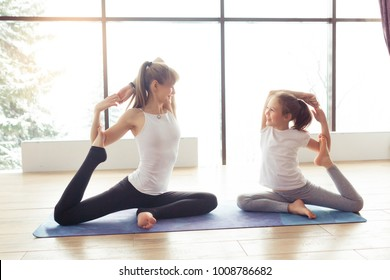 Mother and kid daughter in the gym centre doing yoga poses or stretching fitness exercise near big window with a beautiful scenery with mountains and trees with snow. Healthy family lifestyle concept
