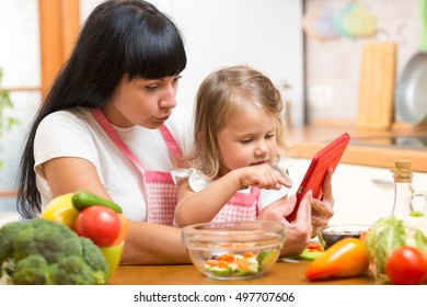 Mother and kid daughter prepare recipe in kitchen.