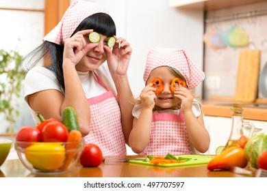 mother and kid daughter preparing healthy food and having fun
