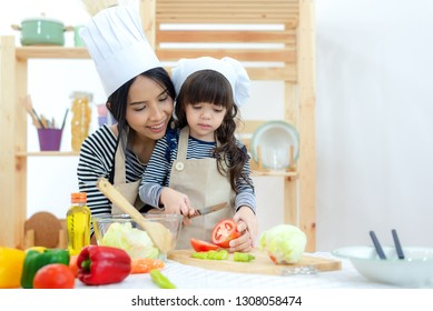 Mother and kid girl cooking and cutting fresh vegetables on kitchen, happy and relax in holiday at hose.  Lifestyle Family Concept