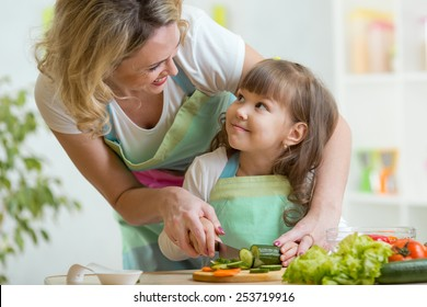 mother and kid girl cooking and cutting vegetables on kitchen