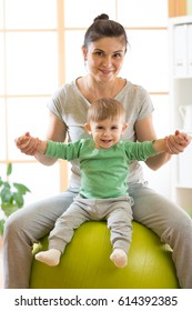 mother and kid having fun with gymnastic ball